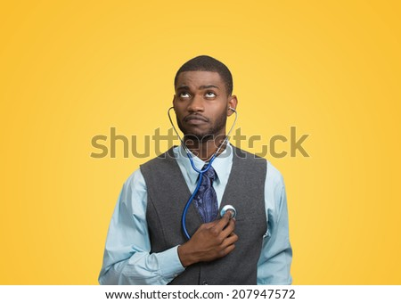 Closeup portrait executive man, business person, worker listening to his heart with stethoscope looking up isolated yellow background. Preventive medicine, financial condition concept. Face expression - stock photo