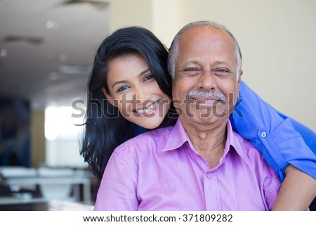 Closeup portrait, family, young woman in blue shirt holding older man in pink collar button down from behind, happy isolated indoors home background - stock photo