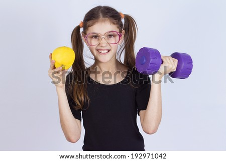 Closeup portrait fit, happy, smiling, funny little girl holding dumbbell, apple, pumping up muscles isolated grey background. Healthy life style, choice concept, Positive human emotions, attitude