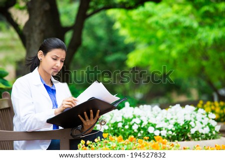 Closeup portrait, friendly, young serious confident female doctor, healthcare professional checking patient notes, bills isolated outside green trees, white flowers background. Health care reform. - stock photo