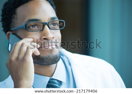 Closeup portrait, friendly, young smiling confident male doctor, healthcare professional talking on phone, isolated indoor clinic hospital background. Patient visit, good news. Positive emotion - stock photo