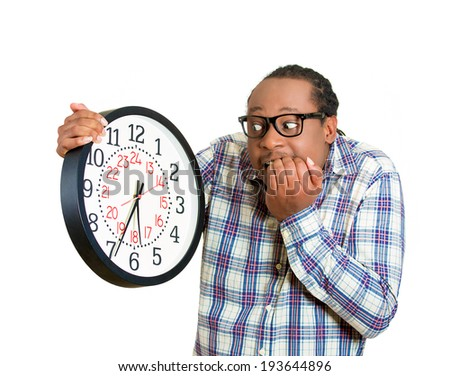 Closeup portrait funny looking man with glasses student, leader holding wall clock, stressed biting fingernails pressured by lack, running out of time, late meeting, isolated white background. Emotion - stock photo