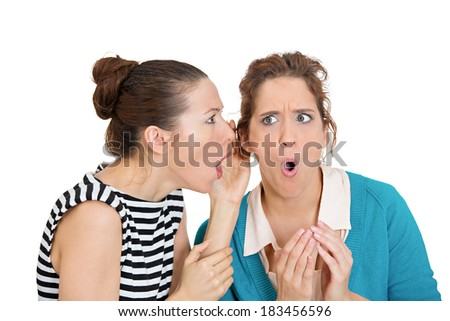 Closeup portrait, girl whispering into woman ear telling her something secret, disturbing, slander. Shocked surprised disgusted annoyed mad response. Negative human emotion facial expression feeling