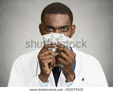 Closeup portrait grumpy greedy miserly health care professional, male doctor holding, protecting his money dollars in hand, isolated black background. Negative human emotion facial expression attitude - stock photo