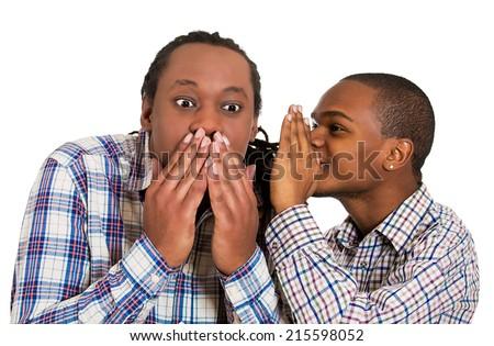 Closeup portrait guy whispering into man's ear telling him something funny, shocking. Shocked response. Human communication, emotions, facial expression, feelings, body language, perception - stock photo