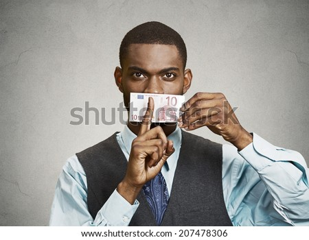Closeup portrait handsome corrupt guy, businessman holding euro bill currency to mouth, showing shhh sign, isolated grey background. Bribery concept in politics, business, diplomacy. Face expressions - stock photo