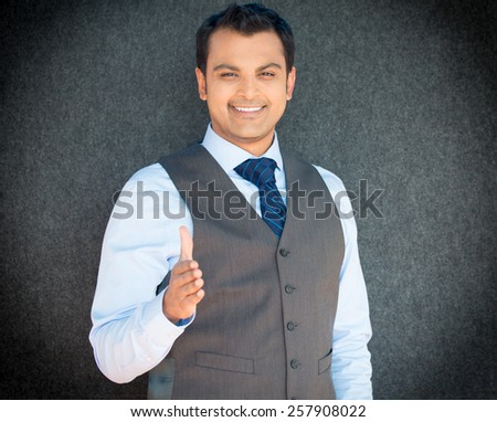 Closeup portrait handsome happy smiling young business man, confident student, entrepreneur, giving handshake, isolated gray background. Positive face expressions, emotions, feelings, attitude - stock photo