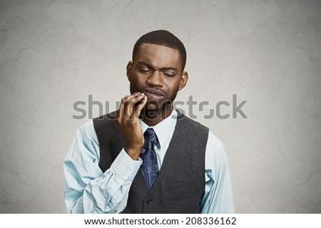 Closeup portrait handsome sad young executive man, student, worker touching face having bad pain, tooth ache, isolated grey background. Negative human emotions, facial expressions, feeling reaction - stock photo