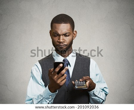 Closeup portrait handsome, serious looking worried businessman reading bad news on smart phone holding mobile, calculator isolated grey background. Human face expression, emotion, corporate executive  - stock photo