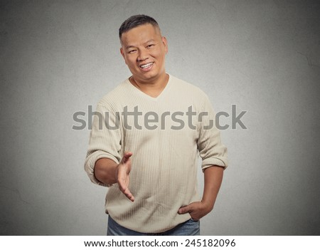 Closeup portrait handsome young adult smiling man giving extending arm for handshake at camera gesture isolated grey wall background. Positive emotion facial expression feeling attitude perception - stock photo