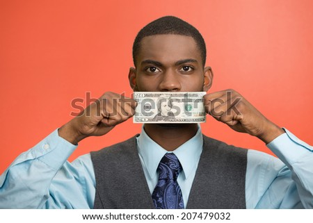 Closeup portrait handsome young corrupt corporate man in blue shirt holding twenty dollar bill to mouth, isolated red background. Bribery concept in politics, business, diplomacy. Life perception - stock photo