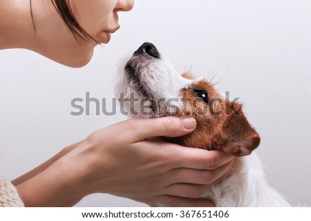 Closeup portrait handsome young hipster woman, kissing her good friend dog on grey background. Positive human emotions, facial expression, feelings - stock photo