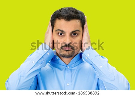 Closeup portrait, handsome young man covering, closing his ears with hands, eyes observing, closed mouth, isolated green background. Hear no evil concept. Human emotion, facial expression - stock photo