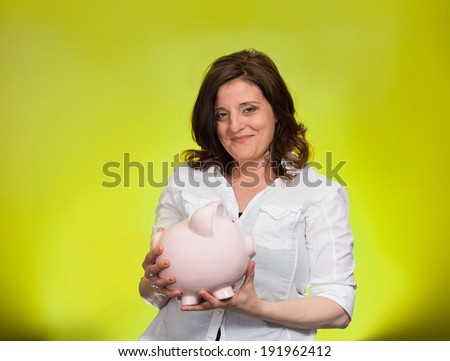 Closeup portrait, happy beautiful business woman, bank employee, showing, holding piggy bank, isolated green background. Financial savings concept. Positive human emotion, facial expression, attitude