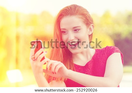 Closeup portrait, happy, cheerful, girl, excited by what she sees on cell phone, isolated city park background. Facial expression, reaction. Woman sending text message from her mobile. Instagram style - stock photo