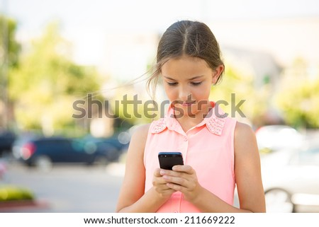 Closeup portrait happy, cheerful, girl, teenager texting on cell phone isolated outdoor street background. Positive Facial expressions, reaction. Teen sending text message from her mobile device - stock photo