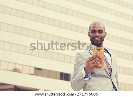 Closeup portrait, happy, cheerful man excited by what he sees on cell phone, isolated outdoor background corporate office. Facial expression, reaction. Businessman sending text message from his mobile - stock photo