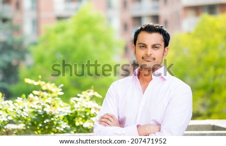 Closeup portrait, happy handsome man in pink shirt, arms folded, crossed, standing outside of his office during sunny day, isolated balcony background of green trees.  - stock photo