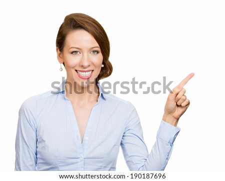 Closeup portrait, happy, pretty, confident, young smiling business woman gesturing, pointing space at left, isolated white background. Positive human emotion, signs symbol, facial expression feelings