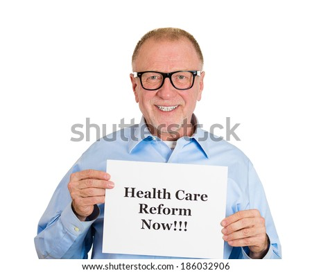 Closeup portrait, happy senior mature business man, corporate employee holding health care reform now! sign, isolated white background. Government, federal politics, congress, insurance policy debate - stock photo