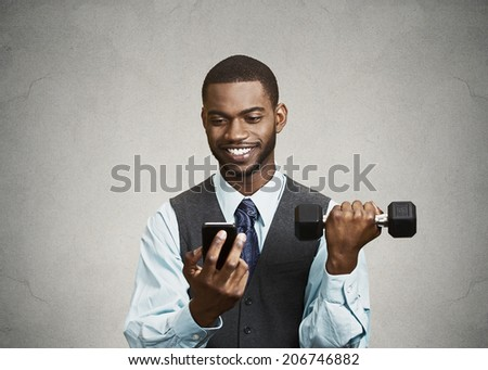 Closeup portrait happy, smiling business man reading good news on smart phone, holding mobile, lifting weight, dumbbell isolated black background. Human face expression, emotion, corporate executive - stock photo