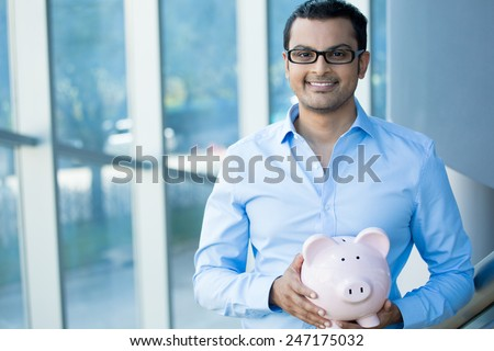 Closeup portrait happy, smiling businessman with black glasses, holding pink piggy bank, isolated indoors office background. Financial budget savings, smart investment concept - stock photo