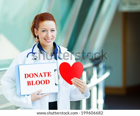 Closeup portrait happy smiling female health care professional woman doctor, transfusion medicine specialist holding sign donate blood, red heart isolated hospital hallway background. Patient plan - stock photo