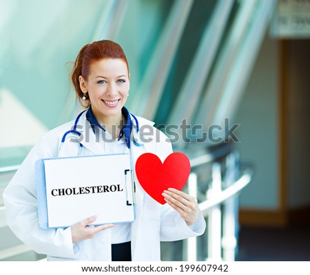 Closeup portrait happy smiling female health care professional, woman family doctor, cardiologist with stethoscope holding sign cholesterol, heart isolated hospital hallway background. Patient plan - stock photo