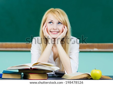 Closeup portrait happy, smiling female student, teacher, sitting at desk in classroom, looking up, daydreaming, thinking, isolated background green chalkboard. Positive facial expressions, emotions - stock photo