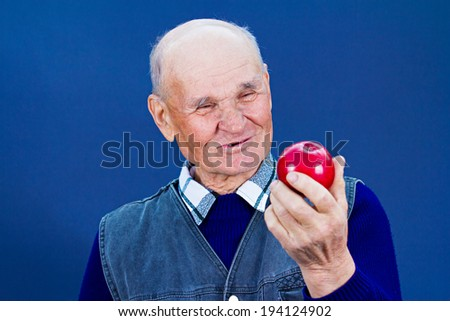 Closeup portrait happy, smiling , healthy, senior, elderly man holding, looking at apple, isolated, black, dark blue background. Human emotions, facial expressions, life perception good diet choices - stock photo