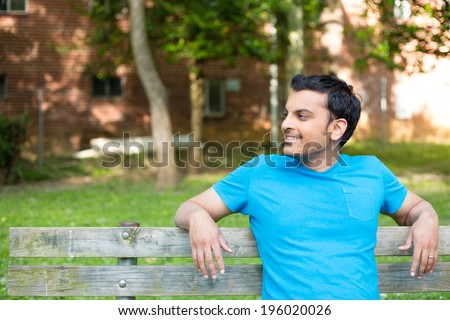 Closeup portrait, happy smiling, regular young man in blue shirt sitting on wooden bench, relaxed looking to side, isolate background trees, woods - stock photo