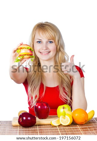 Closeup portrait happy smiling young, fit female holding, eating vitamin fruit sandwich, burger made of apples oranges strawberries fruits giving thumbs up isolated white background. Healthy lifestyle