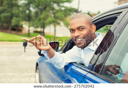 Closeup portrait happy, smiling, young man, buyer sitting in his new blue car showing keys isolated outside dealer, dealership lot, office. Personal transportation, auto purchase concept - stock photo