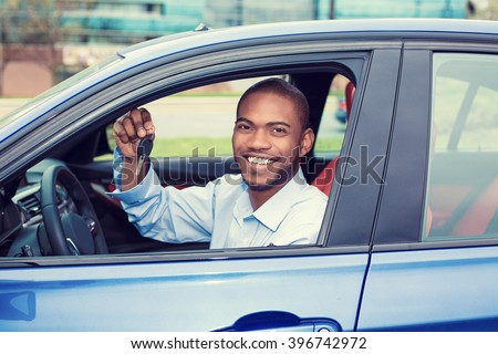 Closeup portrait happy, smiling, young man, buyer sitting in his new blue car showing keys isolated outside dealer, dealership lot. Personal transportation, auto purchase concept - stock photo