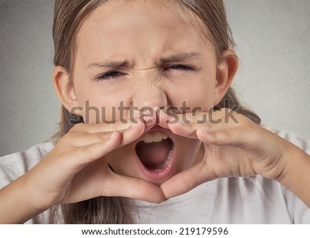 Closeup portrait, headshot angry, upset, hostile, furious teenager girl yelling, screaming, hands to mouth isolated grey wall background. Negative human emotions, facial expression reaction attitude - stock photo