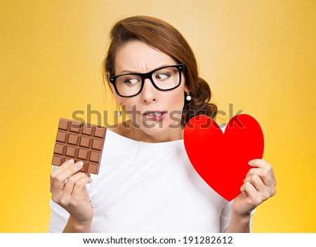 Closeup portrait, headshot beautiful, young nerd woman with black glasses holding heart craving square milk chocolate isolated yellow background. Food diet option dilemma. Sweet temptation. Expression - stock photo