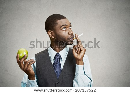 Closeup portrait headshot corporate executive businessman making bad health choices, smoking cigarette instead of having fresh green apple isolated black background. Face expressions, body language - stock photo