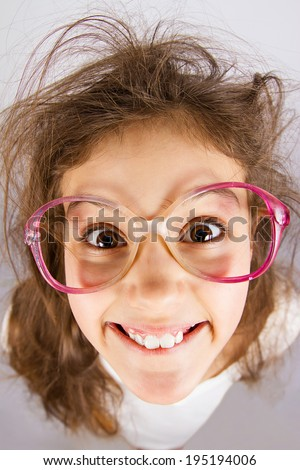 Closeup portrait, headshot happy, smiling , excited, funny looking, little girl with big glasses, messy hair, isolated grey background. Positive human emotions, facial expressions, attitude, reaction - stock photo