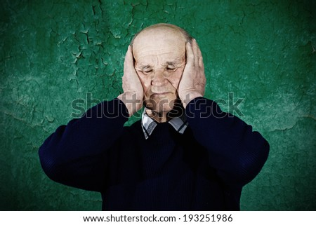 Closeup portrait, headshot, senior mature, peaceful, tranquil, relaxed, old man covering his ears, closed eyes, isolated green wall background. Hear no evil concept. Human emotions, facial expressions - stock photo