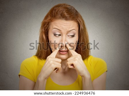 Closeup portrait headshot woman pinches nose with fingers hands looks with disgust away something stinks bad smell situation isolated grey wall background. Human face expression body language reaction - stock photo