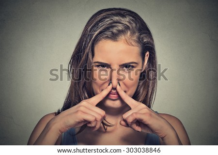 Closeup portrait headshot woman pinches nose with fingers hands looks with disgust something stinks bad smell situation isolated on gray wall background. Human face expression body language reaction  - stock photo
