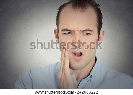 Closeup portrait headshot young man with sensitive tooth ache crown problem suffering from pain touching outside mouth with hand isolated grey background. Negative emotions, facial expression, feeling - stock photo