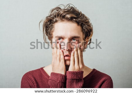 Closeup portrait, headshot young tired, fatigued business man worried, stressed, dragging face down with hands Negative human emotions, facial expressions, feelings - stock photo