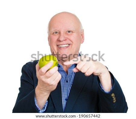 Closeup portrait, healthy, happy senior man nutritionist, energetic grandfather holding, offering apple as diet alternative, isolated white background. Positive emotions, facial expression. Nutrition - stock photo