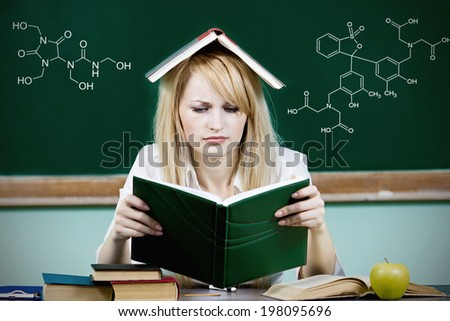 Closeup portrait hopeless overwhelmed student sitting at desk, reading book studying preparing finals isolated chalkboard background with chemistry formulas. Education college concept. Face expression - stock photo