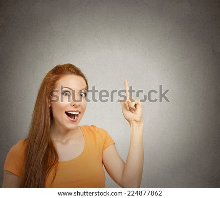 Closeup portrait intelligent excited young woman who just came up with idea aha isolated grey wall background with copy space. Positive human emotion facial expression feeling perception body language - stock photo