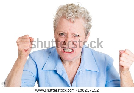 Closeup portrait, mad, angry, upset, hostile, senior mature woman, worker, furious employee, fists in air, isolated white background. Negative emotions, facial expression reaction