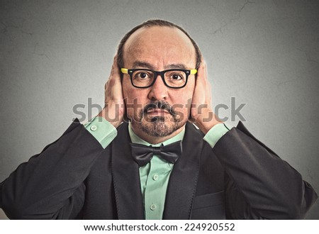 Closeup portrait middle aged business man with glasses covering his ears with hands closed mouth isolated grey wall background. Hear no evil concept. Human emotion facial expression life perception - stock photo