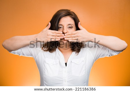 Closeup portrait middle aged woman covering closed mouth. Speak no evil concept, isolated orange background. Negative human emotion facial expressions, sign, symbol. Media news coverup, censorship  - stock photo