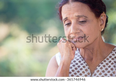 Closeup portrait, morose elderly lady, downcast gloomy, resting face on hand, isolated green outdoors background - stock photo